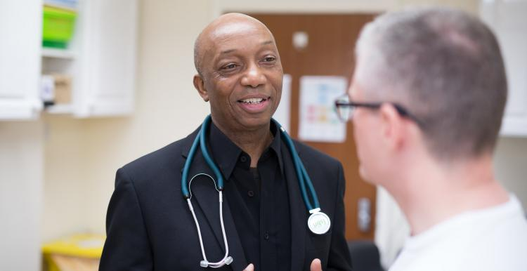 Male doctor speaking to a male patient