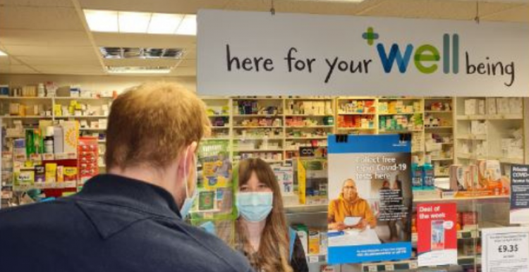 Image of a man talking to a woman in a Well pharmacy