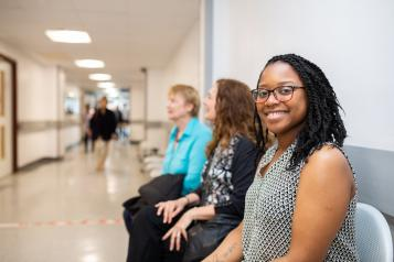 Woman sitting on a chair in a hospital corridor smiling to camera
