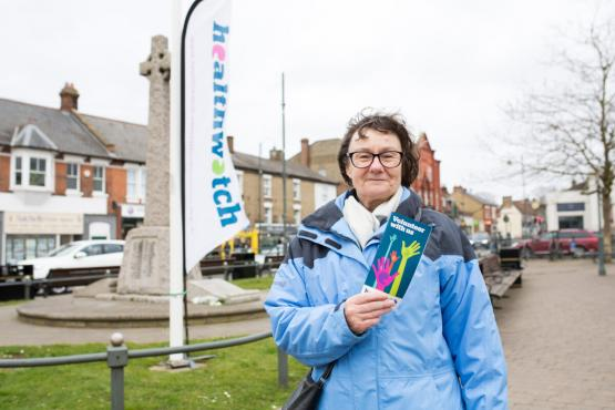 a woman standing in front of a Healthwatch banner, holding a Healthwatch leaflet